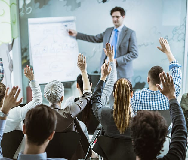 Raised hands in adult learning class